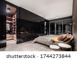 Small photo of Elegant bedroom with walk in closet behind stylish, black and mirrored wall