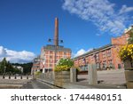 Wooden embankment with steps and flower beds against the background of a red brick factory with a large chimney on the shore of lake Vesiyarvi in the city of Lahti. Finland.