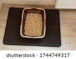 Small photo of Cat toilet on the litter mat. There is wood pellet cat litter in the toilet.