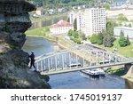 Woman climbing steep wall above river and town, via ferrata route, Shepherd