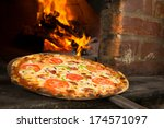 pizza entering a wood oven | Shutterstock . vector #174571097