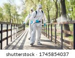 Small photo of Sanitization, cleaning and disinfection of the city park due to the emergence of the Covid19 virus. Specialized team in protective suits and masks at work. Horizontal shot