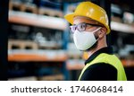 Technician or engineer with protective mask and helmet standing in industrial factory. - stock photo