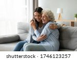 Small photo of Happy multi-generational family sitting on couch in living room, elderly grandmother snuggle to grown up granddaughter, adult daughter missed mature mom, holidays, events, Mother Day congrats concept