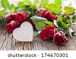 white heart shape and red roses on wood - stock photo