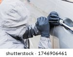 The thief uses a screwdriver Stealing a car at the door handle. The vehicle insurance concept. - stock photo
