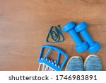 Small photo of Blue color tools for training, sport and activity. Two dumbbells, chesty expanders, measure tape, sneakers, and exercise yoga mat at home. Top view, copy space. Fitness healthy and sport concept