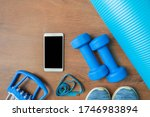 Small photo of Two dumbbells, chesty expanders, measure tape, sneakers, phone and exercise yoga mat at home. Blue color tools for training, sport and activity. Top view, copy space. Fitness healthy and sport concept