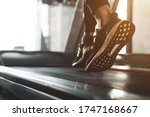 Small photo of Young athlete wearing black sport shoes running on treadmill. He training for cardiovascular endurance and good health with personal trainer in fitness center.