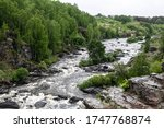 Beautiful landscape with big stones in water riffle of mountain river. Powerful water stream among boulders in mountain creek with rapids. Fast flow among rocks in highland brook. Trees by the river