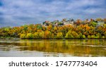 Beautiful view of the Missouri River and its high bank in early evening in fall; observation deck appears on top of the bluff; colorful woody bluffs reflect in water