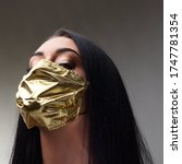Small photo of haughty woman wearing a golden face mask - concept of surgical masks price rise when they are mandatory and as extremely rare as they are needed to mitigate the COVID19 virus pandemic spread