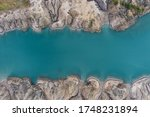 an abandoned coal pit flooded with turquoise water photographed from above