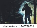 Mysterious Men with Flashlight in His Hand In Dark Foggy Forest. Poacher, Hunter or Rescuer During Rescue Action. - stock photo