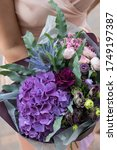 Small photo of Beautiful blossoming flowers (roses, hydrangeas, carnations, eustoma) in blu, purpure and pink colours at the florist shop
