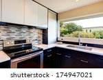 Stock photo black and white modern kitchen room with multi color backsplash 174947021