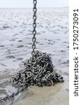 Small photo of Anchor chain of a beached boat during ebb tide in the mudflats near the island of Juist