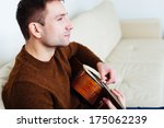 Young man sitting on a sofa and playing guitar - stock photo