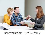 Young couple receiving the keys from an estate agent - stock photo