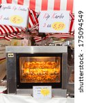 ZWOLLE, THE NETHERLANDS - FEBRUARY 1, 2014: Chicken roasting at the street market in Zwolle. In the Netherlands there are 18,000 merchants realizing a 2.6 billion turn over. - stock photo