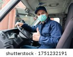 Small photo of Masked truck driver giving thumbs up during coronavirus pandemic