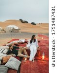 Small photo of Stylish european couple in love enjoying evening together in luxury glamping camp in Sahara desert, Morocco. Romantic mood, lying on multicolor pillows.