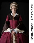 Small photo of A young Tudor woman in a red and brown dress and a French hood