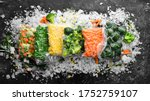Assortment of frozen vegetables on ice. Stocks of food. Top view. Free space for your text.