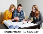 Young couple discussing the blueprints with an architect - stock photo