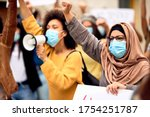Small photo of Muslim woman wearing protective face mask and supporting anti-racism movement with group of people on city streets.