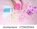 Small photo of Set of depilation and beauty on pink background concept - sugar paste or hair removal waxing melted paste and stripes, orchid and female hands. Film Wax Granules or hot wax, cartridge, wooden spatula