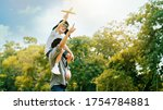 Small photo of Lifestyle Asian family Father and son sat on his shoulders and run in park. Paper plane as a toy in hand of kid And there are many big trees in garden Is natural in the morning of summer