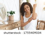 Small photo of Sensitive Skin Treatment. Cheerful Afro Woman Applying Moisturising Soothing Cream At Elbow Zone, Pampering Herself At Home, Free Space