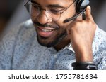 Small photo of Close up face african man telesales worker working wear headset contacting customers to inform them about service, answer questions about products. Call center operator agent, clients support concept
