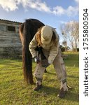 Small photo of A female farrier working on a horse's hoof with a hoof pick. A barn and green grass in the background.