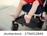 Small photo of Disabled girl sitting in wheelchair. Close up photo of her legs spasticity muscles . Child cerebral palsy. Disability. Inclusion. Family with disabled kid. Family with disabled kid.