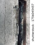 Small photo of Fragment of a concrete pillar with a hole bounded by a metal rectangular insert, close-up. Gray textured surface with cracks and breakaway parts.