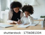 Small photo of African mother helps with task little schoolgirl daughter do together schoolwork, parent explain subject, focused child listen to mum sit at table at home in kitchen. Education, homeschooling concept