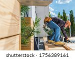 Industrial Theme. Home and Garden. Wooden Porch Building by Caucasian Men in His 30s During Sunny Summer Day. Small Backyard Project. - stock photo
