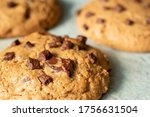 Small photo of Delicious Homemade Chocolate Chip Cookies. Chocolate chip cookies on plate on wooden background. Warm, golden brown, chocolate chip cookies cooling on baking paper. Natural handmade organic cookies.