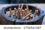 Small photo of Full ashtray of cigarettes butts close-up. Dirty and old wooden ashtray on the old table full of old cigarette and cigar butts. Bangkok Thailand South East Asia