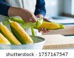 Man Peeling Corn Husk At...