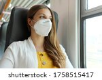 Small photo of Travel safely on public transport. Young woman with KN95 FFP2 face mask looking through train window. Train passenger with protective mask travels sitting in business class looking through the window.