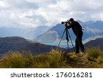 Professional landscape photographer photographing the landscape of New Zealand South Island outdoors. Real people. Copy space - stock photo