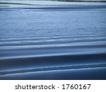 A water background shot of some rolling small waves. - stock photo