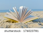 An Open Book Laying On A Sandy...