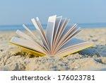 an open book laying on a sandy... | Shutterstock . vector #176023781