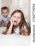 Small photo of Funny and humorous photo of a little girl sister who makes faces and sticks out her tongue because she is being naughty and doesn't want to play with her brother crawling towards her. Impish children