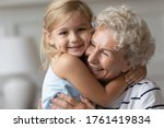 Small photo of Close up image portrait happy small cutie granddaughter hugging with caring old grandmother, multi generational family relatives people snuggle to each other feeling love and strong connection concept