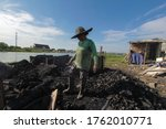Small photo of SEMARANG, INDONESIA - 22 JUNE a female laborer is watching incipient charcoal by the river in the morning on June 22, 2020 Semarang, Central Java, Indonesia